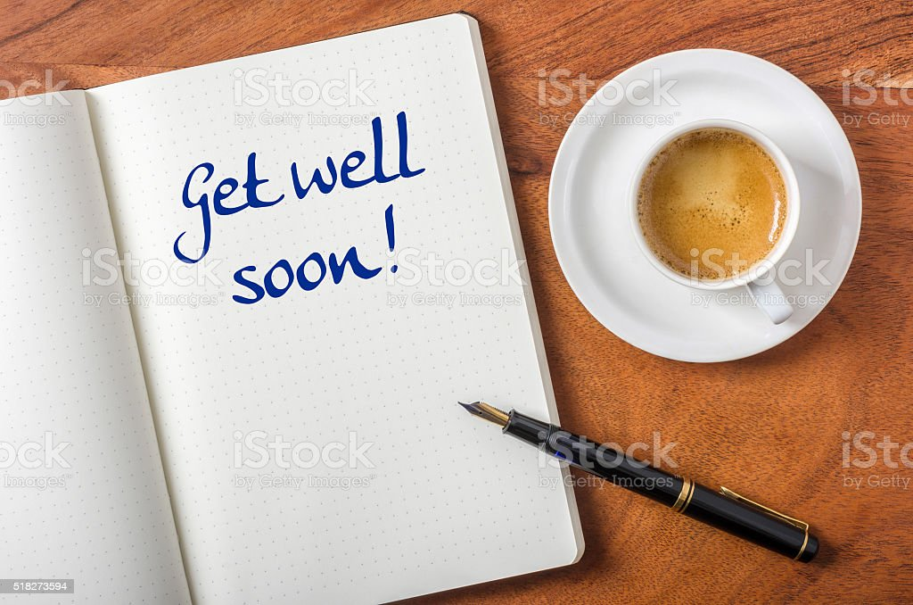 Notebook on a desk - Get well soon stock photo