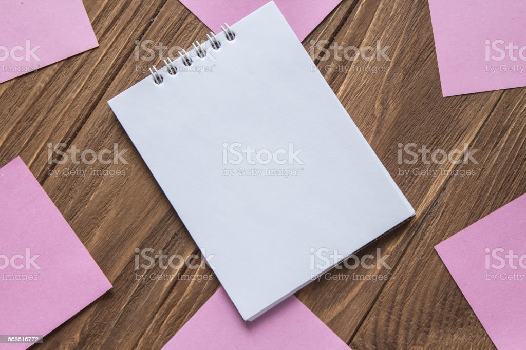 Notebook on wooden background around post-in notes stock photo