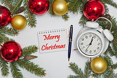 Notebook page with MERRY CHRISTMAS,  decoration and old clock,