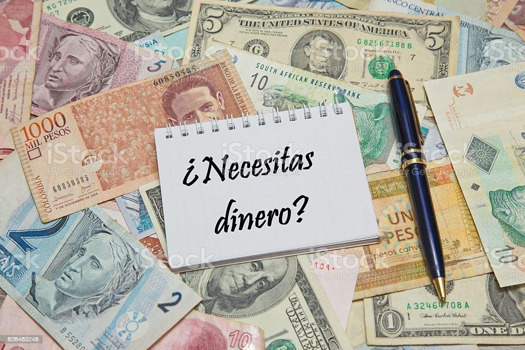 Notebook page with SPANISH text 'NECESITAS DINERO' (NEED MONEY), stock photo