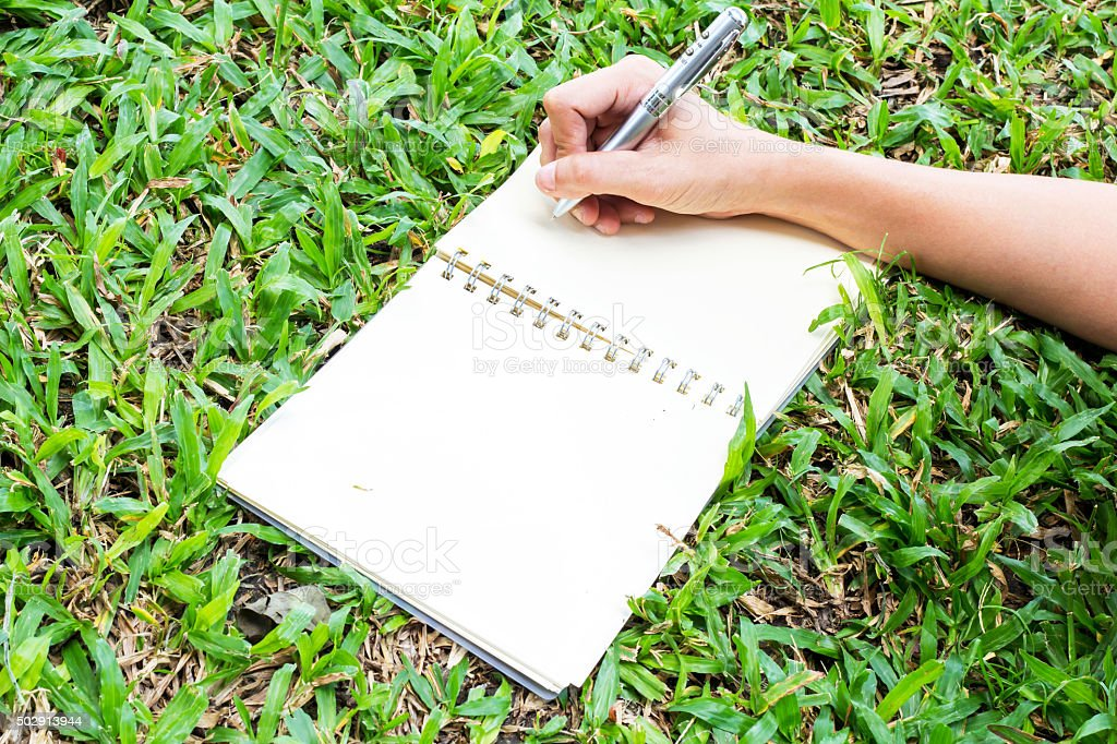 notebook paper  with pencil in hand stock photo