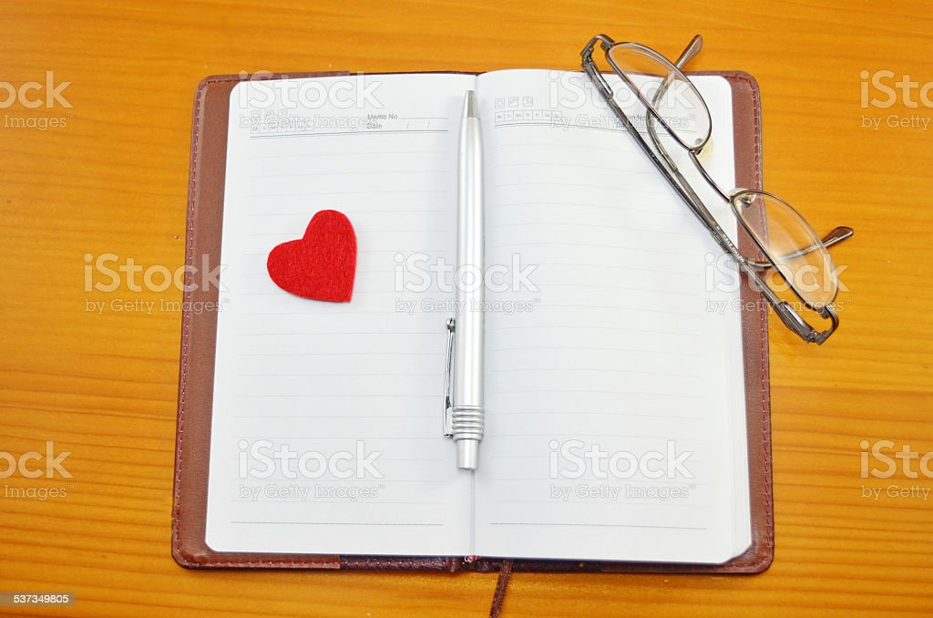 Notebook, pencil and a small red heart on a table royalty-free stock photo