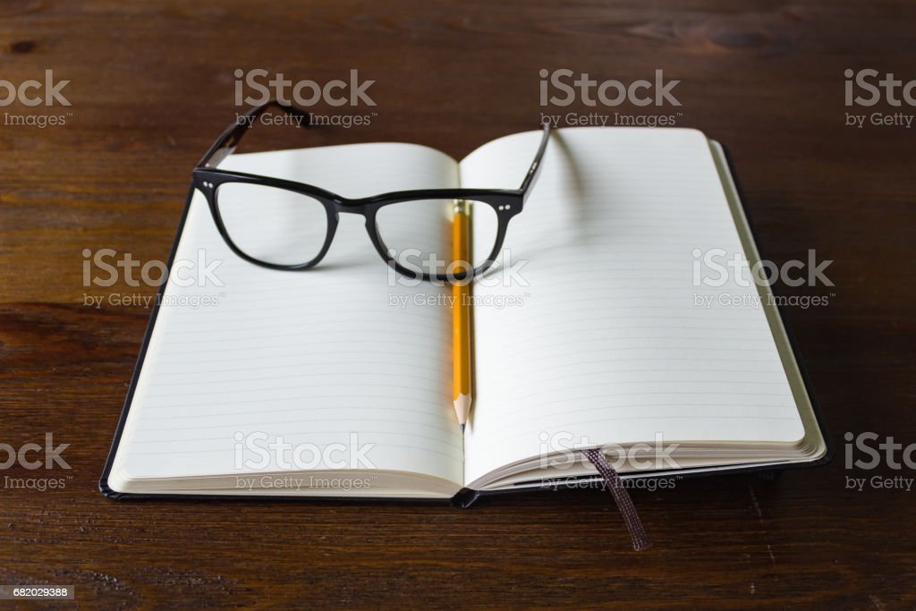 Notebook, pencil, and glasses stock photo