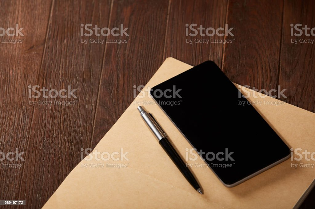 Notebook, telephone and pen on the brown wooden background. stock photo
