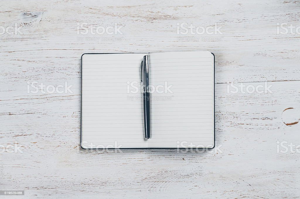 Notebook to write with a pen on white wooden table stock photo