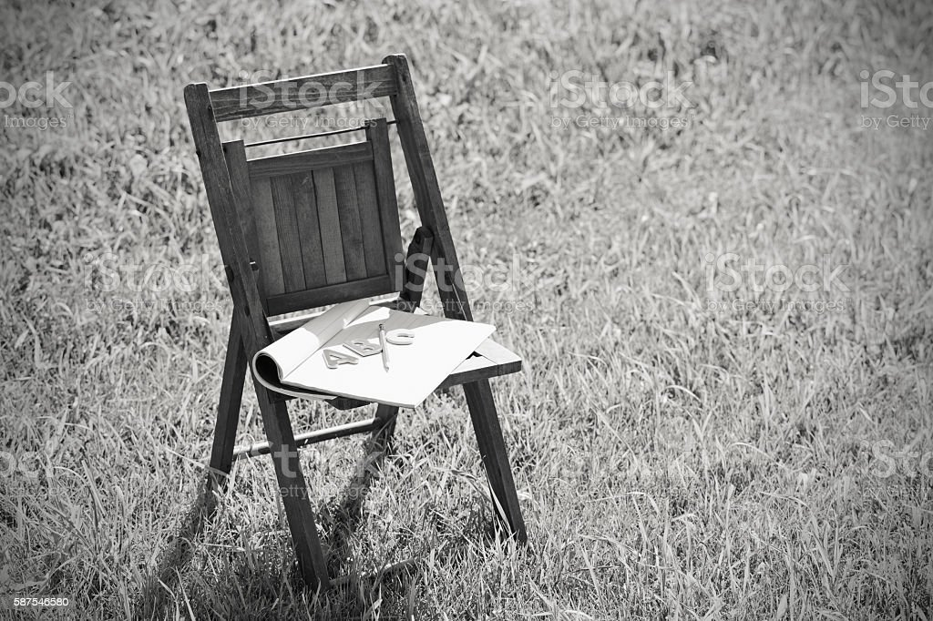 Notebook with ABC Letters and Pencil on Child's Chair stock photo