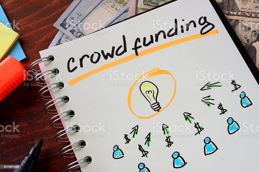 Notebook with crowd funding sign on a table. stock photo