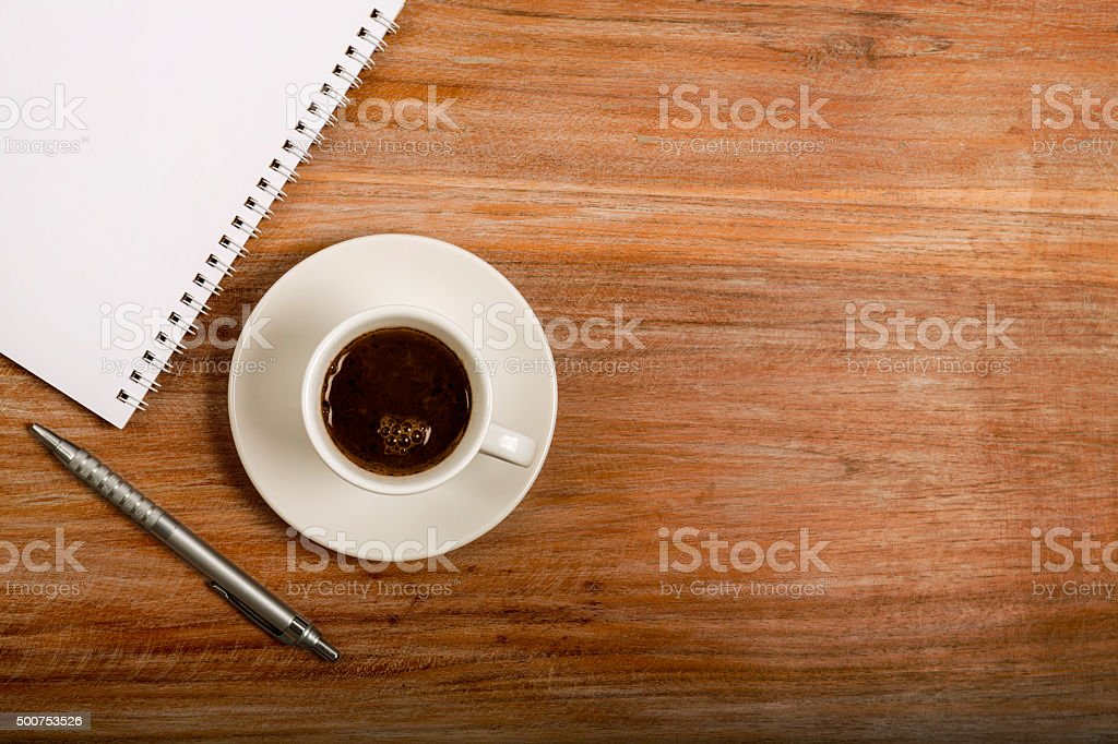 Notebook with cup of coffee on wooden table stock photo