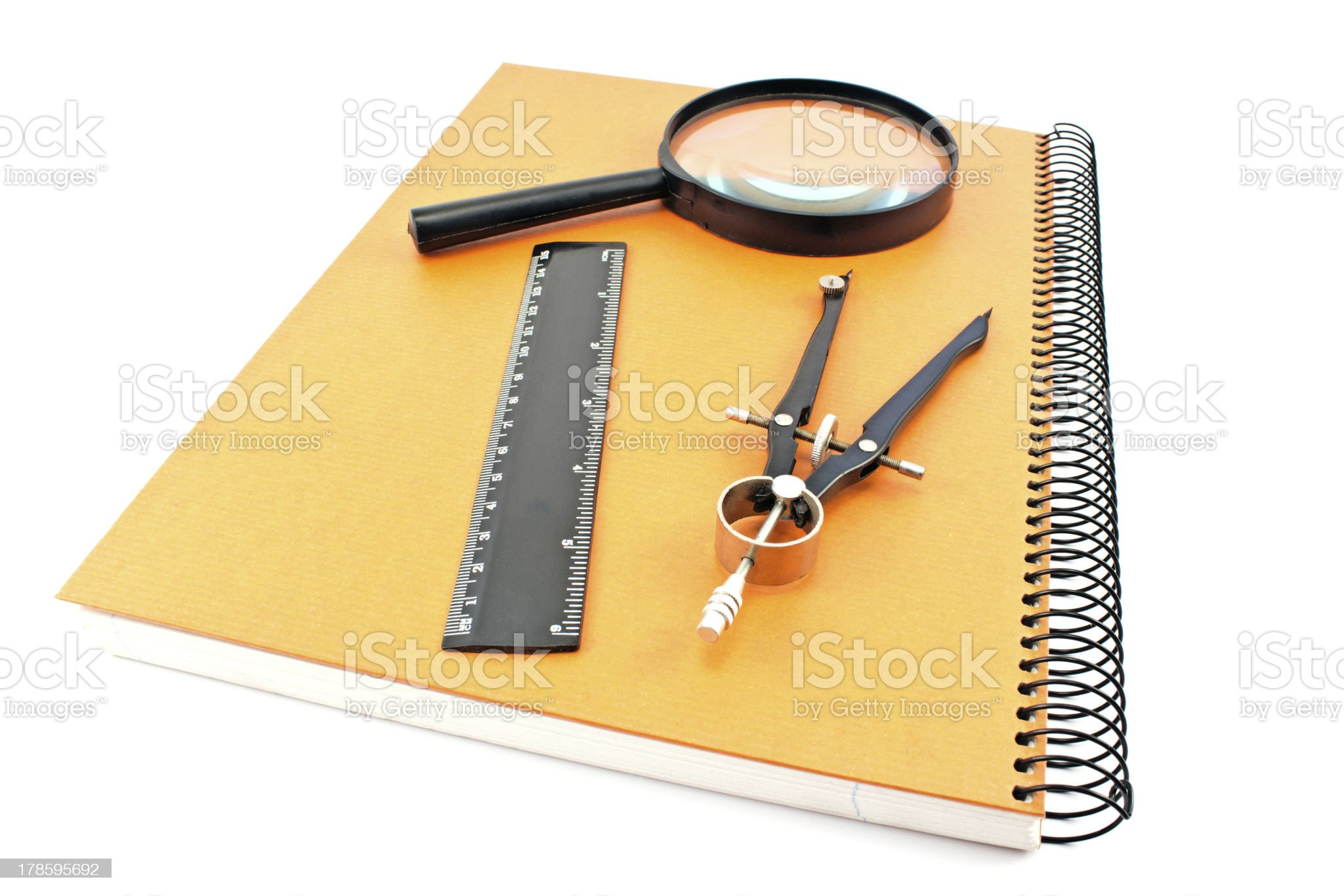 Notebook with drawing compass, ruler and magnifier royalty-free stock photo
