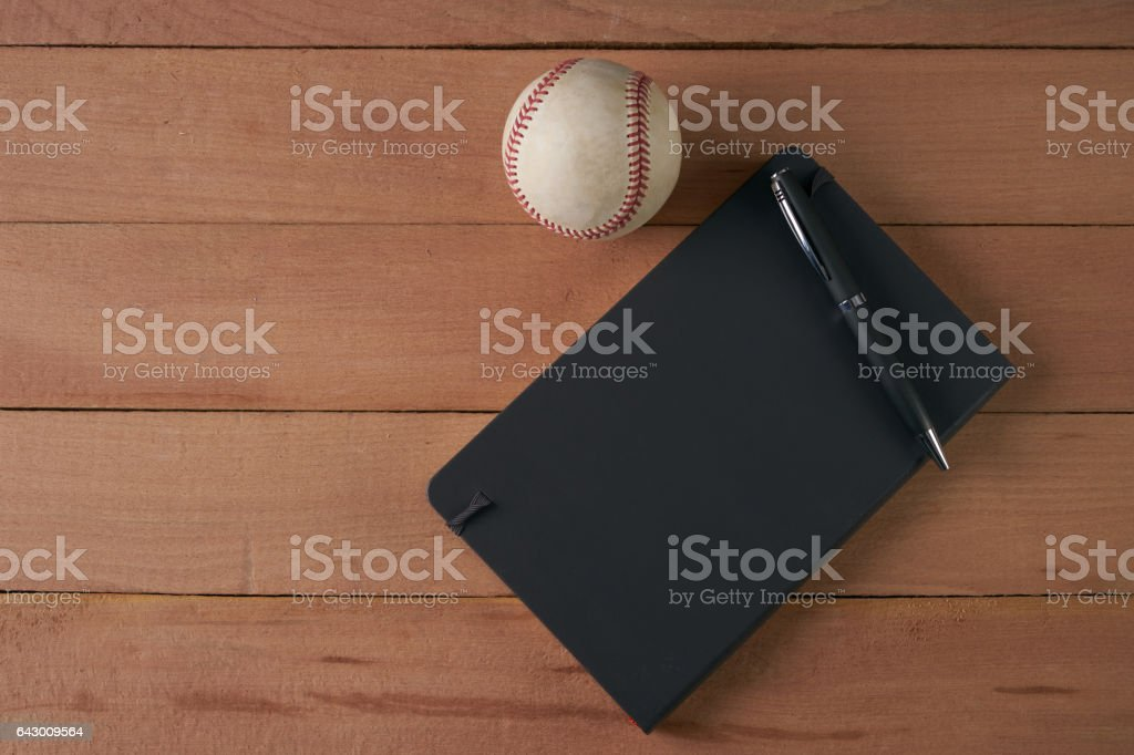 Notebook with pen and baseball ball on an wood table stock photo