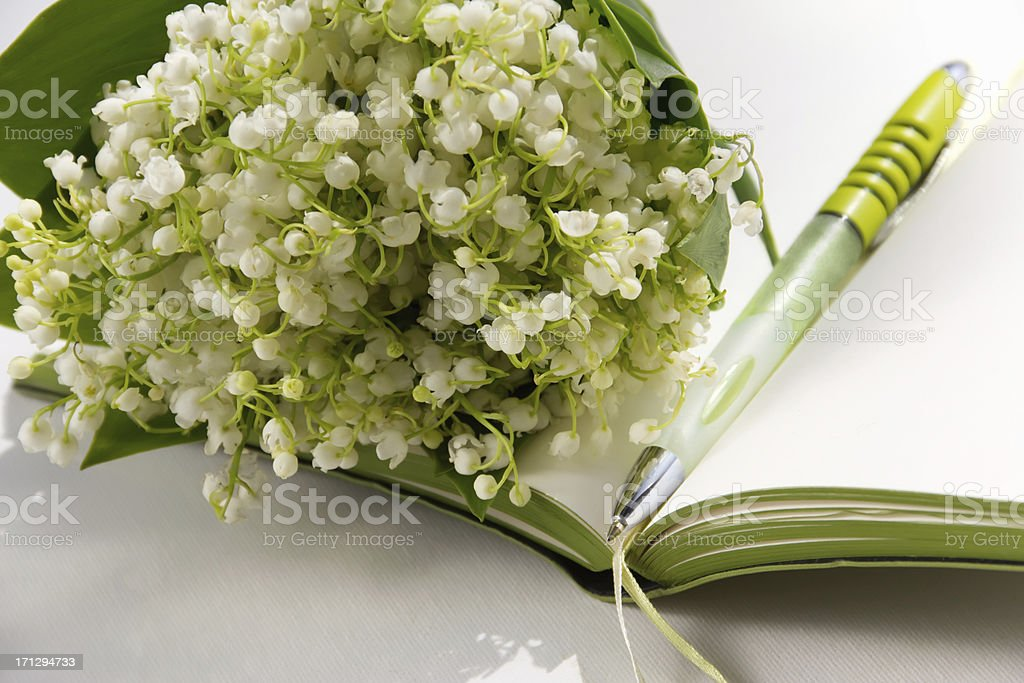 Notebook with pen and flower lilies of the valley royalty-free stock photo