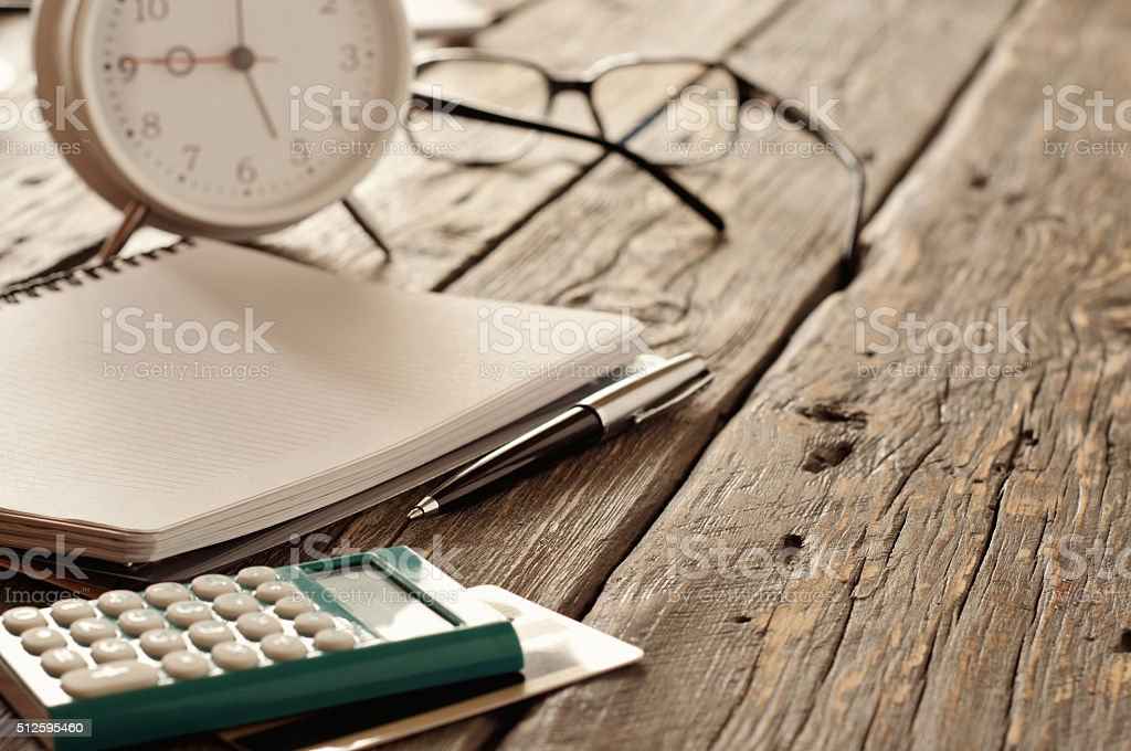 notebook with pen, calculator with credit card and alarm clock stock photo