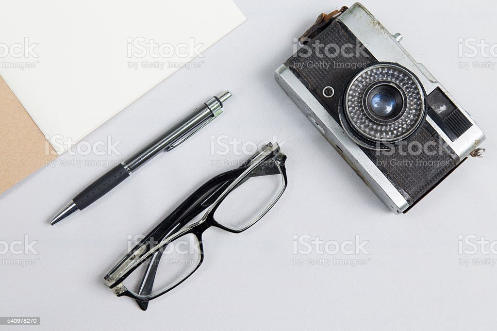 notebook with pen , glasses and camera on desk stock photo