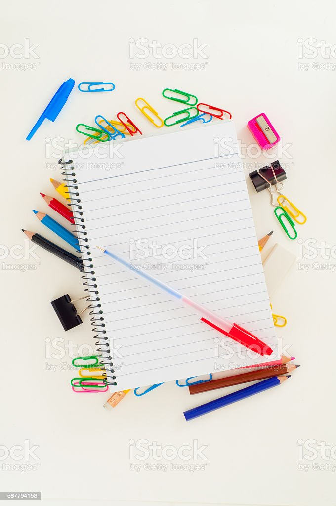 Notebook with pen on top of school stationery stock photo