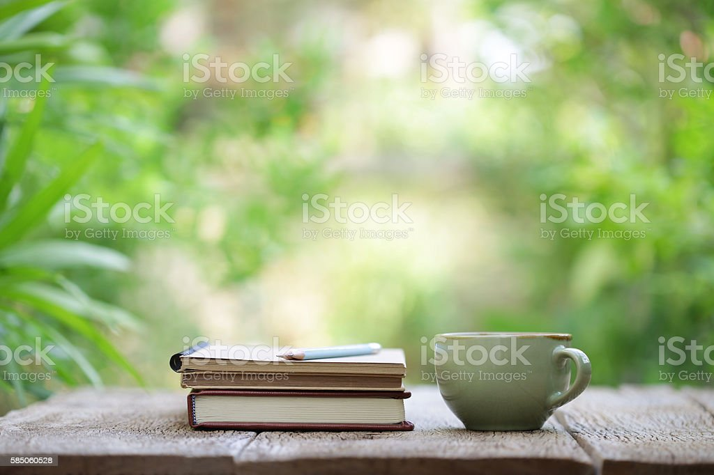 Notebook with pencil and cup on wooden table stock photo