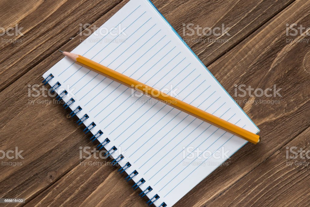 Notebook with pencil on wooden background stock photo
