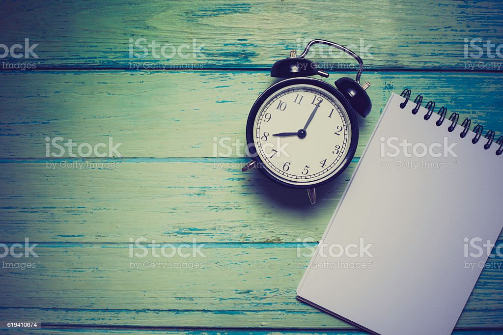 notebook with retro clock on wooden table, top view image stock photo