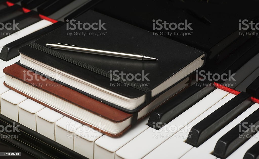 notebook with silver pen on piano keyboard royalty-free stock photo
