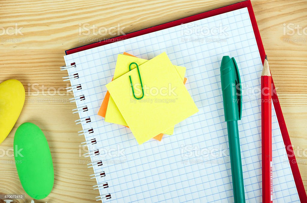 Notebooks, pens, and stickers on wooden background stock photo