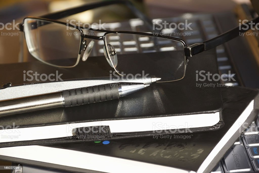 notebooks with pens and glasses on the computer royalty-free stock photo