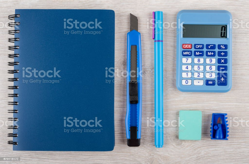 Notepad, calculator and other stationery tools on wooden table stock photo