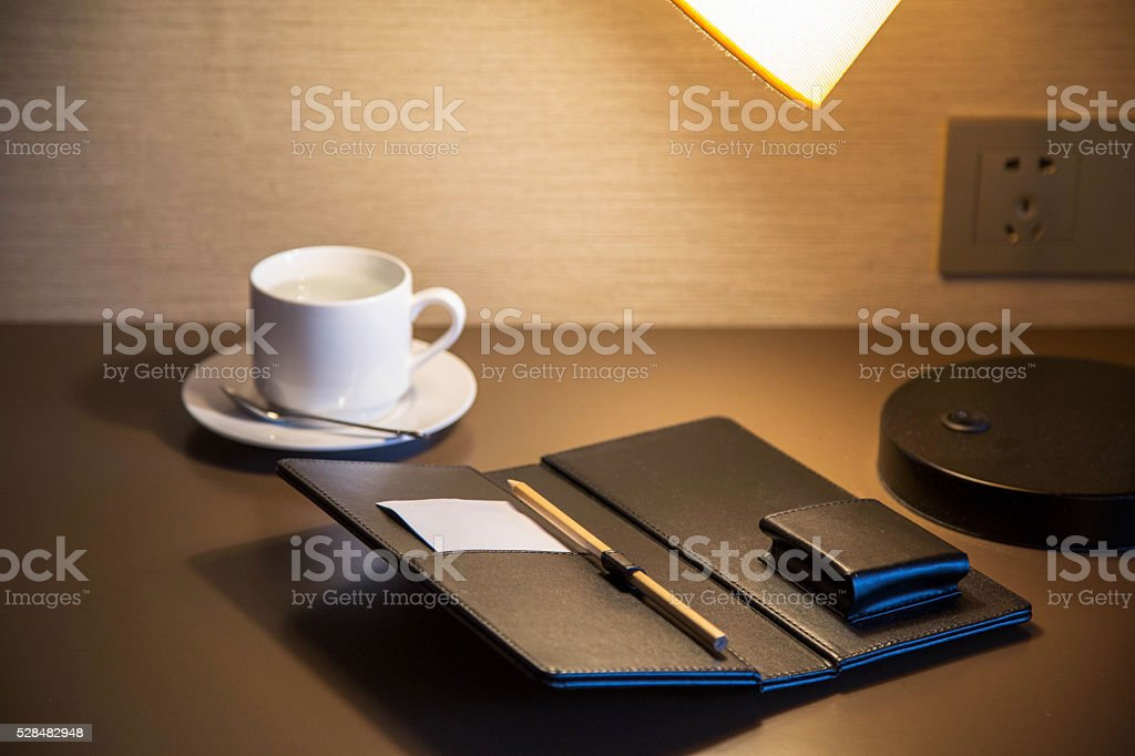 notepad, coffee cup on table, at night stock photo