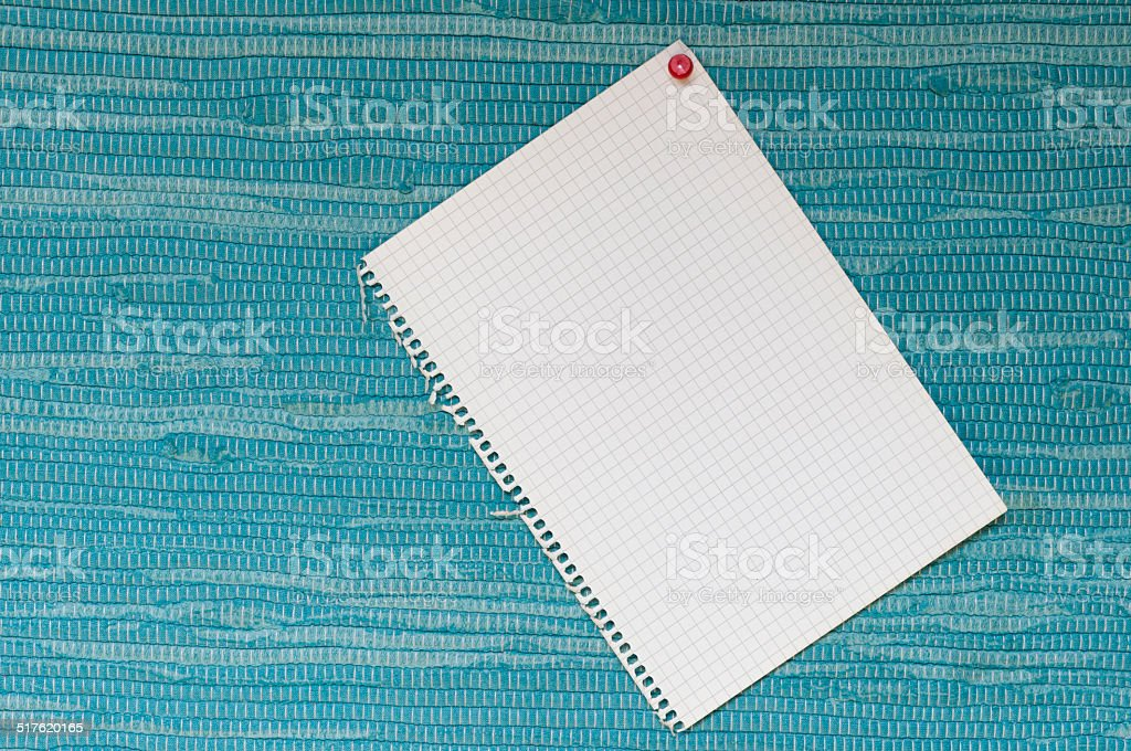 Notepad in front of blue woven fabric stock photo