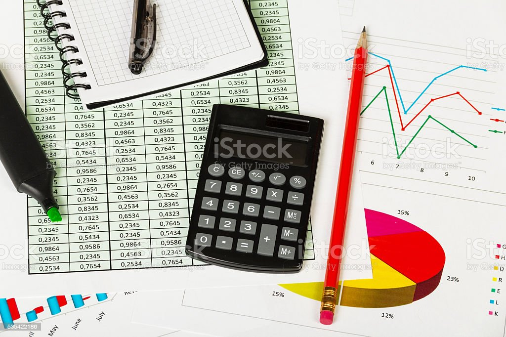 Notepad, pen, marker, pencil and calculator on background of graphs. stock photo