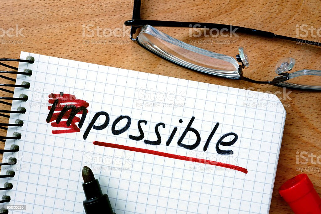 Notepad with converting the word impossible to possible. stock photo
