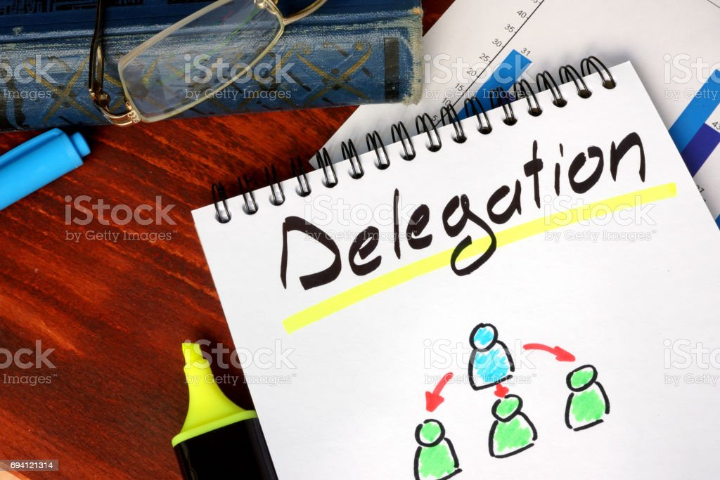 Notepad with Delegation on a wooden surface. stock photo