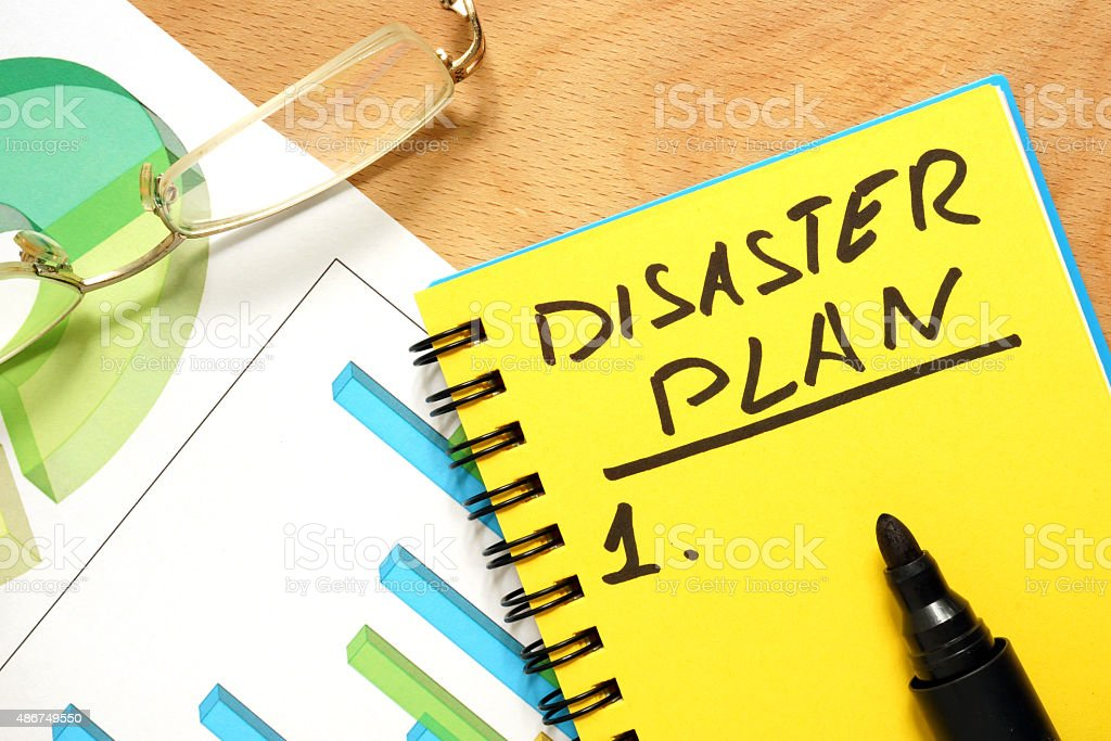 Notepad with disaster plan on a wooden table. stock photo