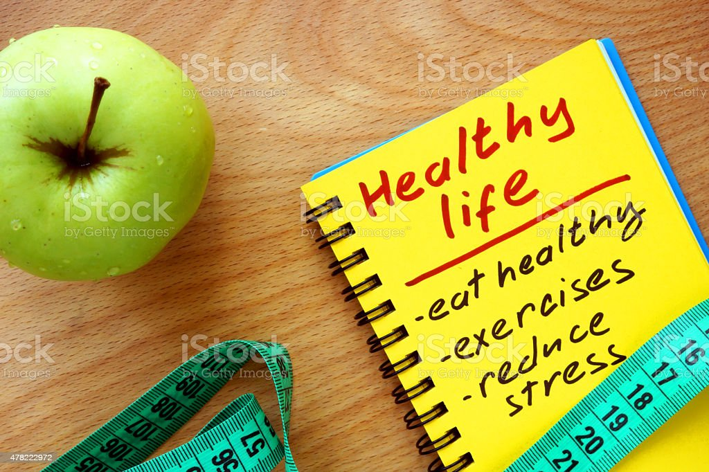 Notepad with healthy life guide, apple and measure tape stock photo