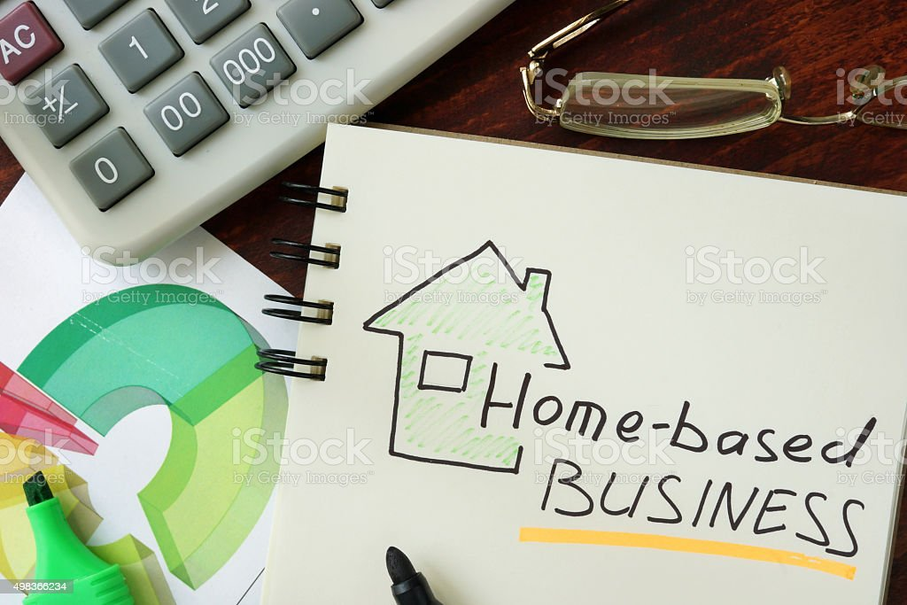 Notepad with Home-based business on the wooden table. stock photo