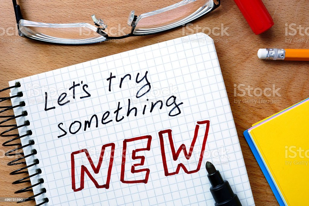 Notepad with  let's try something new  on office wooden table. stock photo