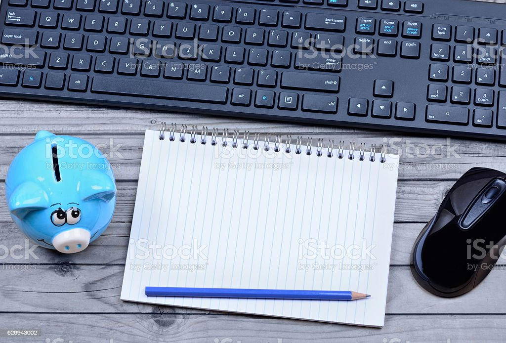 Notepad with piggybank and keyboard pc stock photo