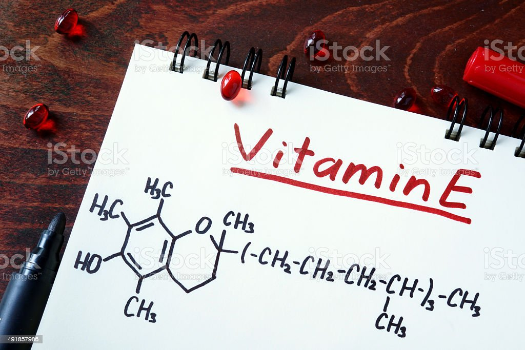 Notepad with  vitamin e and pills on the table. stock photo