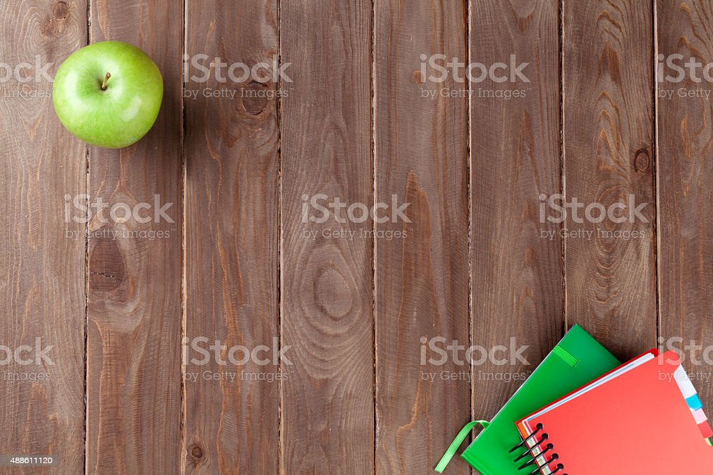 Notepads and apple on table stock photo
