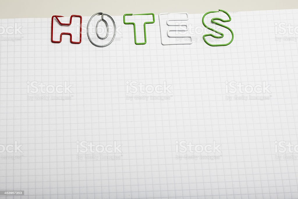 Notes spelled with Paper clip letters on notepad royalty-free stock photo