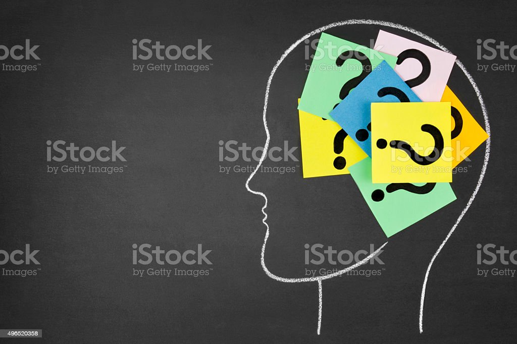 Notes with Question Marks Inside Human Head on Chalkboard stock photo