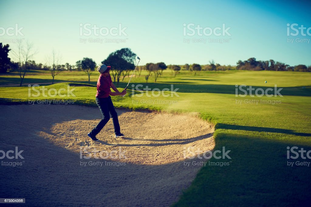 Shot of a young man hitting the ball out of the bunker during a round...