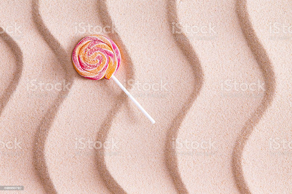 Nothing tastes crunchier than a sandy lollipop at the beach stock photo