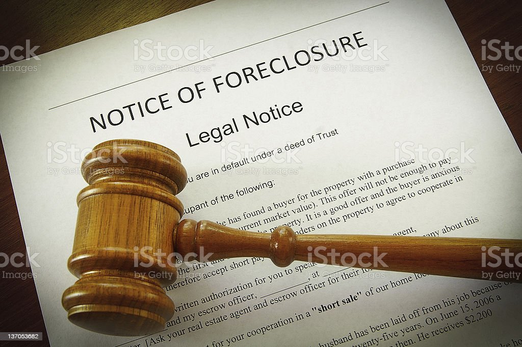 Notice of foreclosure with a wooden gavel on top stock photo