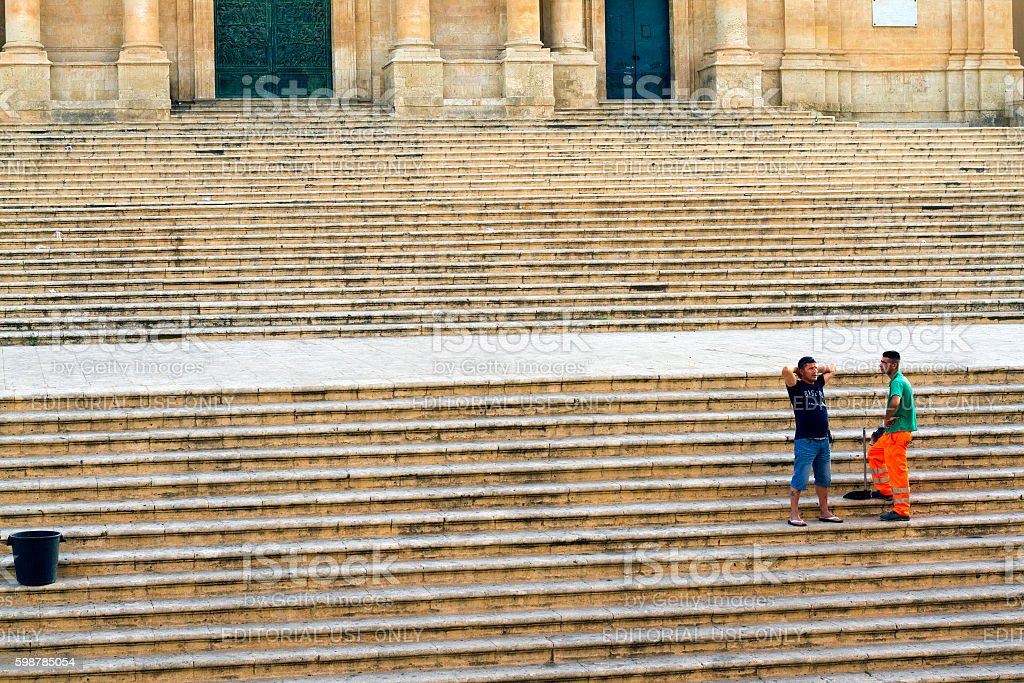 Noto, Sicily: Street Sweeper Chats with Friend on Cathedral Steps stock photo