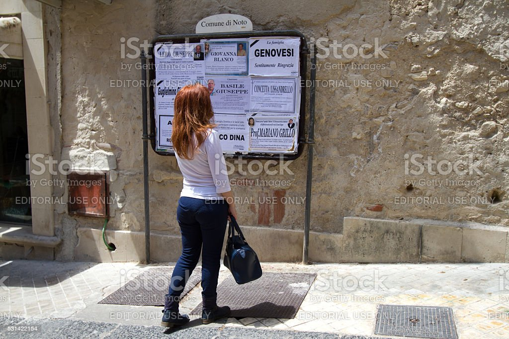 Noto, Sicily: Woman Reads Death Notices stock photo