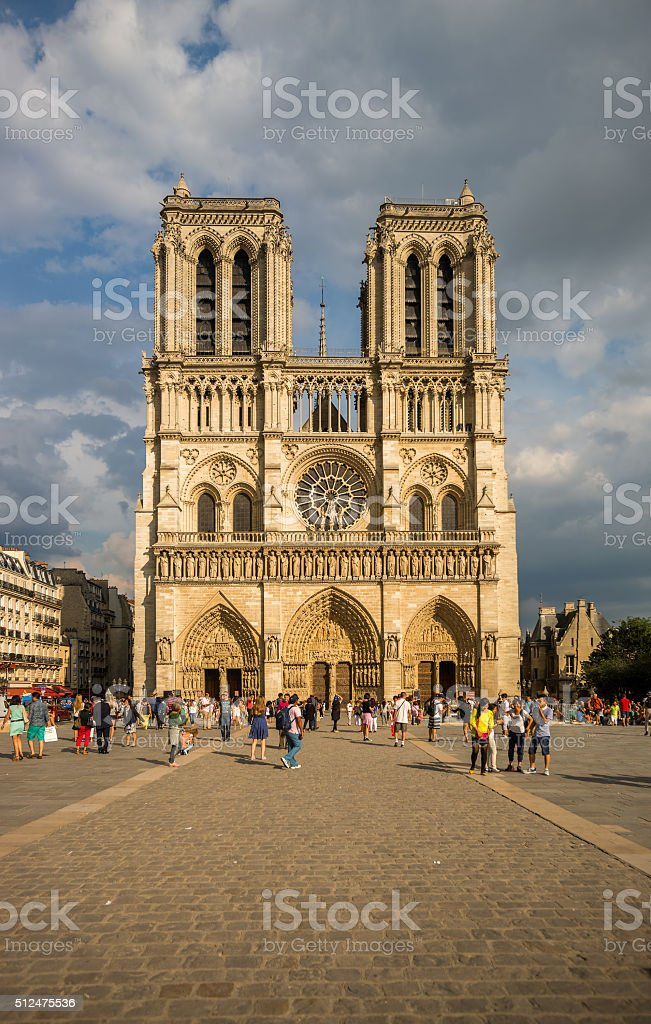 Notre Dame cathedral under puffy clouds stock photo
