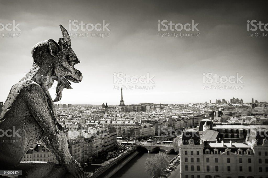 Notre Dame: Chimera (demon) overlooking Paris skyline a summer d stock photo