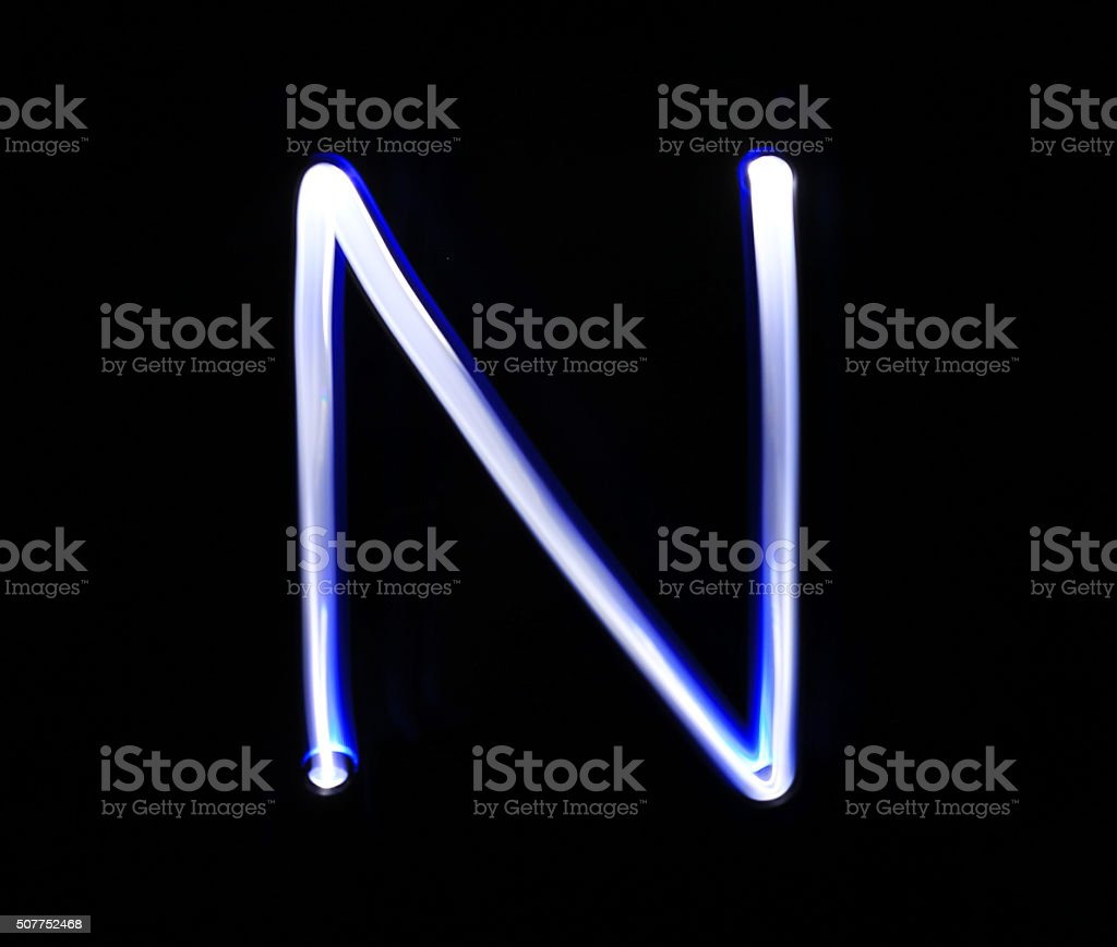 N November alphabet hand writing blue light  over black backgrou stock photo