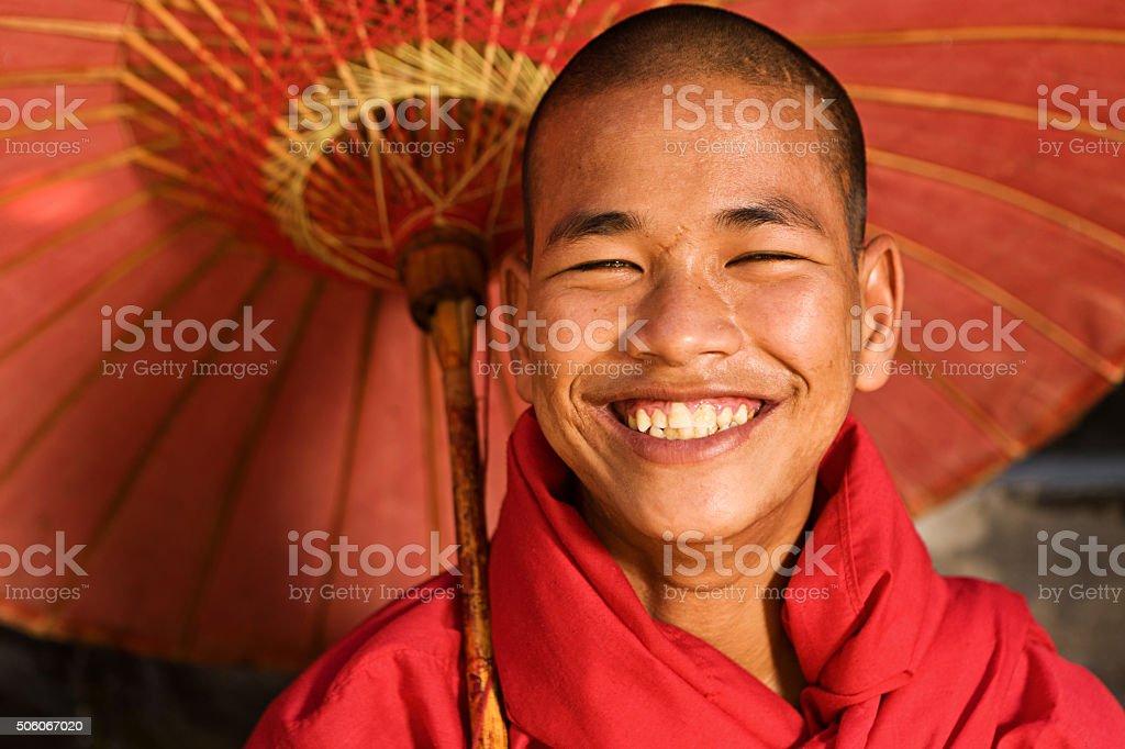 Novice Buddhist monk holding umbrella, Myanmar stock photo