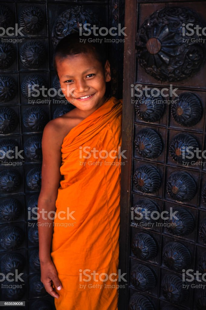 Novice Buddhist monk looking out of the doors, Bhaktapur stock photo