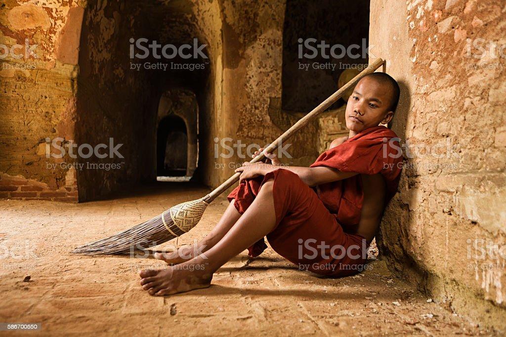 Novice Buddhist monk resting inside the temple. Myanmar stock photo